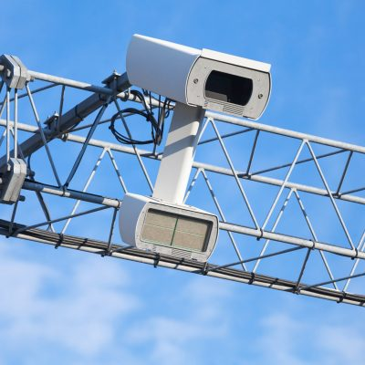 Traffic enforcement camera closeup photo over blue sky
